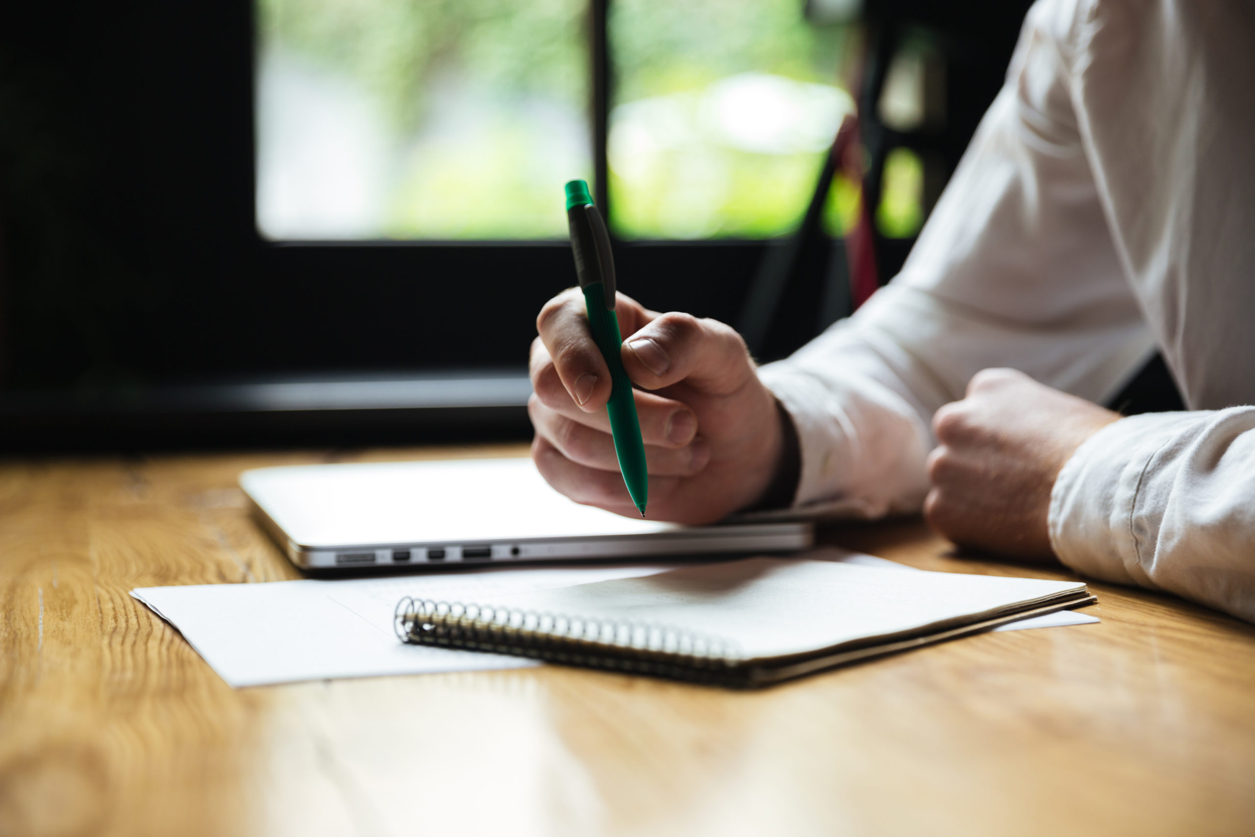 Cropped photo of mans hand holding green pen, while taking notes